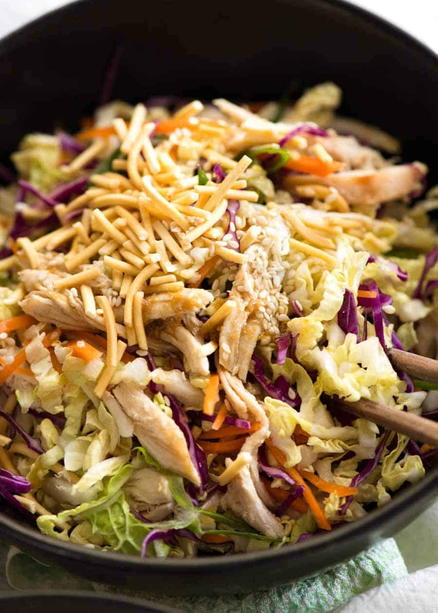 Close up of Chinese Chicken Salad with Asian Dressing in a rustic dark brown bowl, ready to be eaten